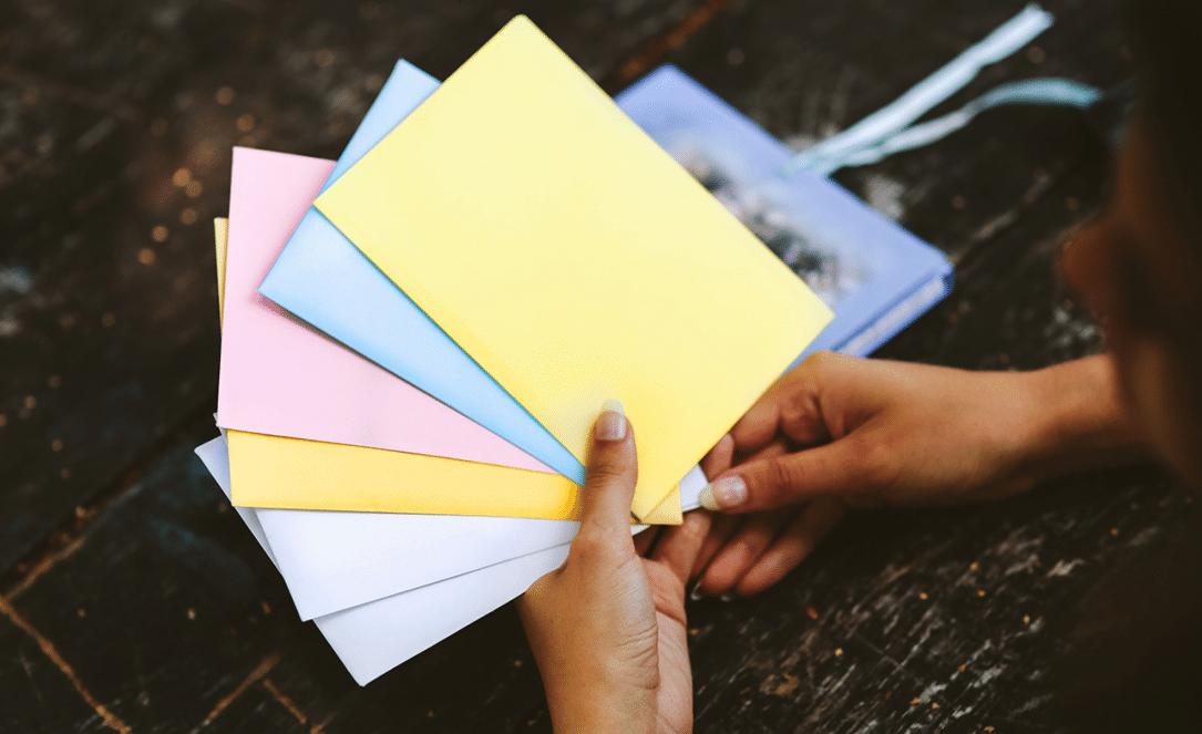 Sparen lernen mit der Umschlagmethode_Hand hält farbige Umschläge